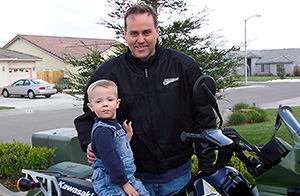 Motorcycle lawyer Frank Penney and his son sitting on a motorcycle outside their home