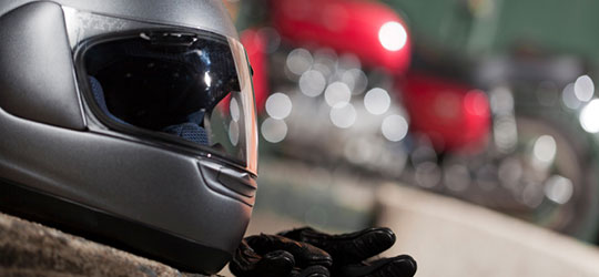 A close up of a motorcycle helmet and gloves. California motorcycle lawyer Frank D. Penney gives biker safety tips