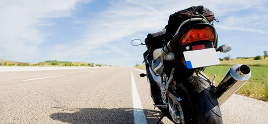 Motorcycle stopped on a wide and empty road. Motorcycle resources can provide tips, communities, and relevant information on riding your bike